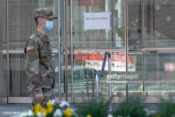 A soldier wearing a protective mask walks past a sign that says No Salute Area in front of the Javitz Center amid the coronavirus pandemic on April...