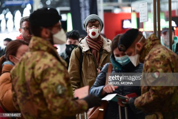 Soldier wearing a respiratory mask control passengers arriving at the Milan Centrale railway station on March 9 2020 as Italy is battling the world's...