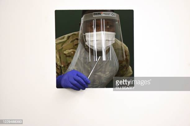 Soldier wearing full PPE waits at a window for a colleague's swab as they practice for the arrival of members of the public inside the mass and rapid...