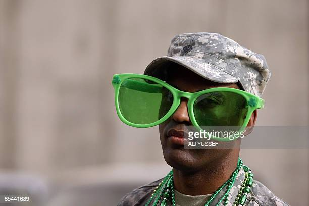 Soldier wearing giant green glasses for Saint Patrick's Day poses for a picture during celebrations of the Irish patron saint at the fortified Green...