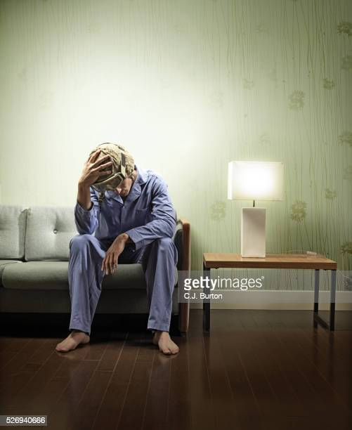 Soldier wearing his combat helmet and pajamas sitting on couch
