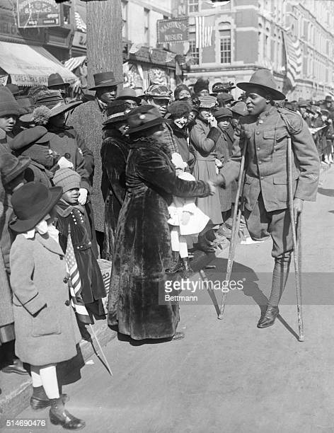 A soldier who lost his leg in World War I shakes hands with the crowd at the Parade of the 36th Colored Infantry