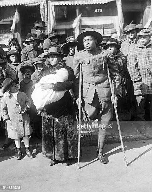Soldier whose leg was amputated due to a war injury watches the victory parade of the 369th infantry in New York, 1919.