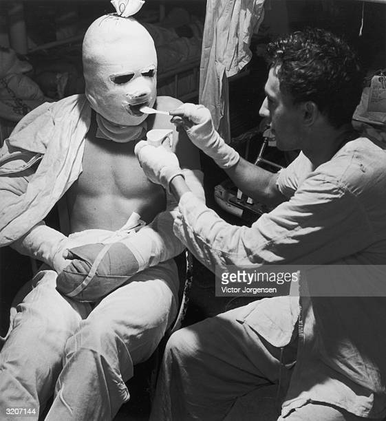 A soldier with bandages over his hands feeds the victim of a Kamikaze attack whose face arms and hands are wrapped in pressure bandages in the...
