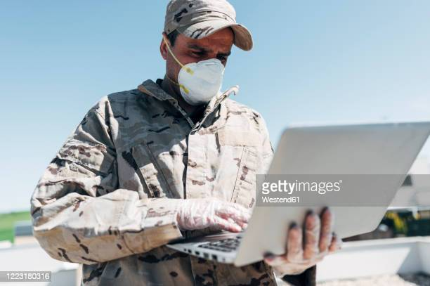 soldier with face mask on emergency operation, using laptop - military stock pictures, royalty-free photos & images