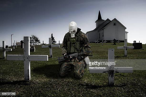 Soldier with gas mask kneeling in cemetery