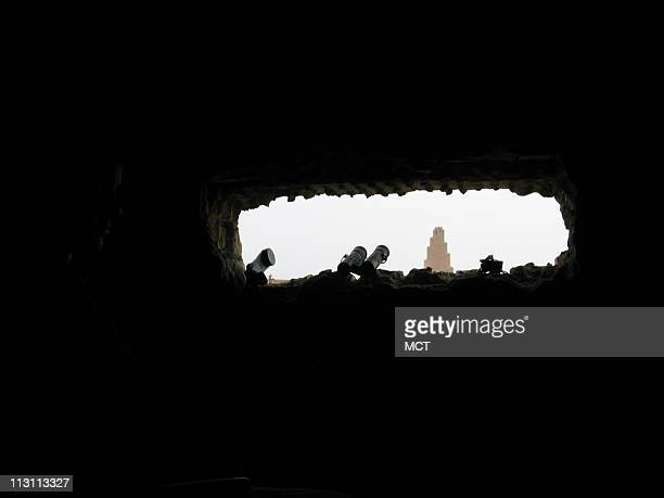 A soldier with the 101st Airborne Division looks out at Samarra from an observation post February 3 2006 In the background stands a mosque minaret...