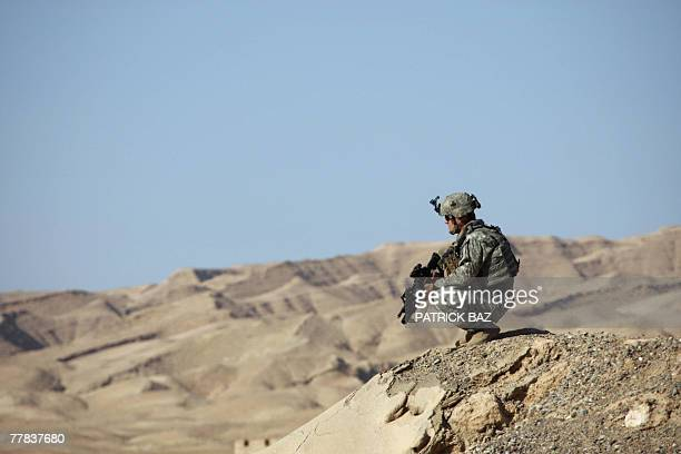 Soldier with the 101st Airborne Division scans the area during an operation searching for weapon caches near the town of Baiji, 10 November 2007. US...