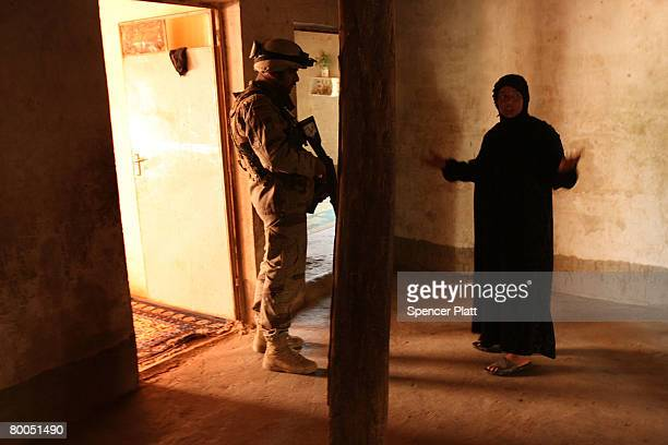 A soldier with the 2nd Brigade of the 5th Iraqi Division of the Iraqi Army speaks with a woman n a village which was purged of insurgents hours...