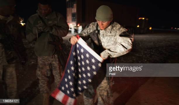 Soldier with the 3rd Brigade Combat Team, 1st Cavalry Division folds up a U.S. Flag outside their Mine Resistant Ambush Protected vehicle before...