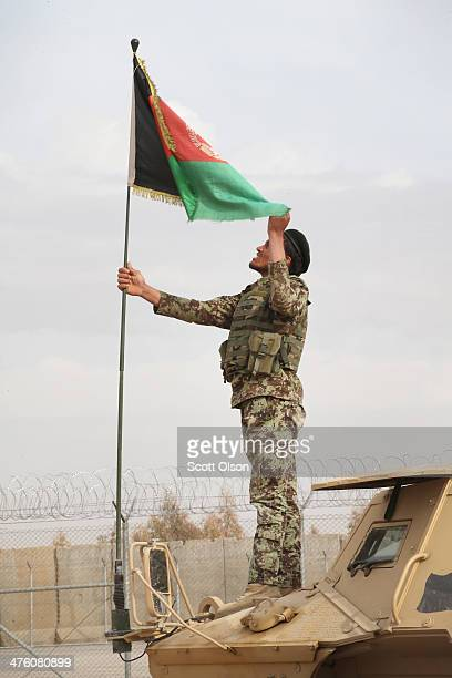 Soldier with the Afghan National Army adjusts the Afghan flag on his vehicle before heading out on a joint patrol with soldiers from the U.S. Army's...