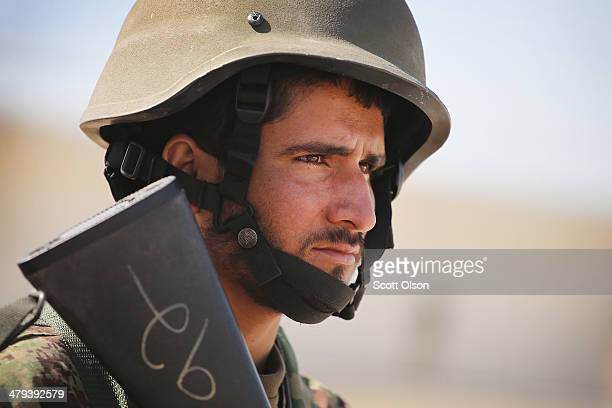 A soldier with the Afghan National Army stands guard during a basic training graduation ceremony at the ANA's Combined Fielding Center on March 18...