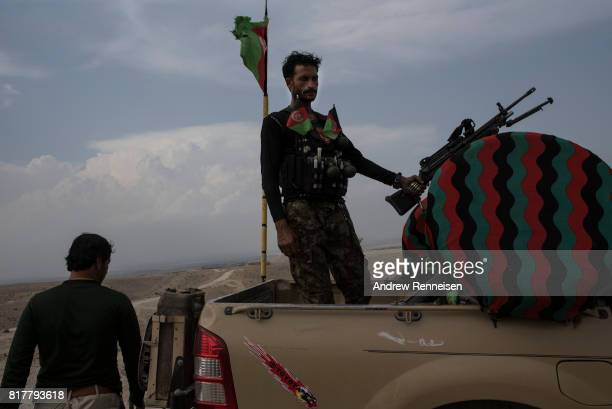 A soldier with the Afghan National Army stands in a truck at an outpost just outside the Momand Valley on July 16 2017 in Achin District Afghanistan...