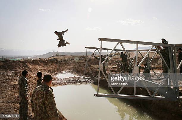 A soldier with the Afghan National Army's National Engineer Brigade tries to make dry land after leaping from the top of a MabeyJohnson portable...