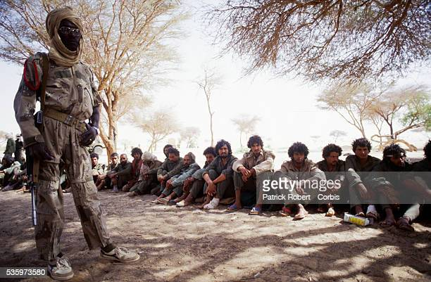 A soldier with the Forces Armees Nationales Chadiennes or National Army of Chad stands guard over Libyan prisoners of war along the road on route to...