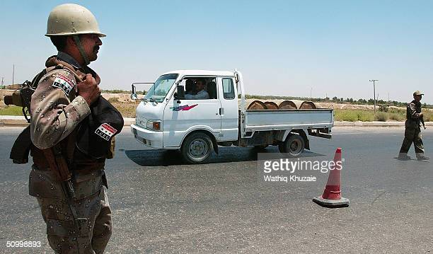 A soldier with the Iraqi Civil Defence Corp mans a checkpoint on the way to the Iraqi city of Baqouba on June 26 2004 near Baqouba Iraq Insurgents...