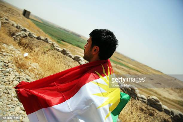 A soldier with the Kurdish peshmerga holds a Kurdish flag at an outpost on the edges of the contested city of Kirkuk on July 3 2014 in Kirkuk Iraq On...