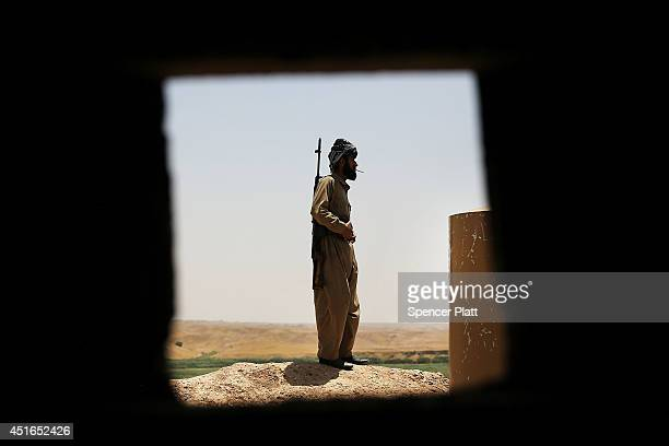 Soldier with the Kurdish peshmerga pauses at an outpost on the edges of the contested city of Kirkuk on July 3, 2014 in Kirkuk, Iraq. On Thursday the...