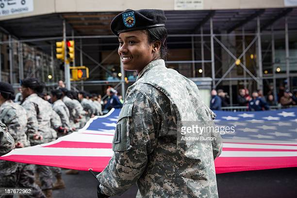 A soldier with the United States Army helps carry a large United States flag while march in the Veteran's Day Parade on November 11 2013 in New York...