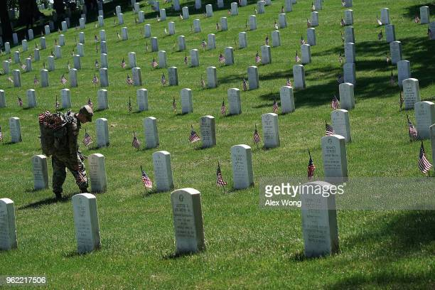 A soldier with the US Army 3rd Infantry Regiment participates in a 'Flags In' event May 24 2018 at Arlington National Cemetery in Arlington Virginia...