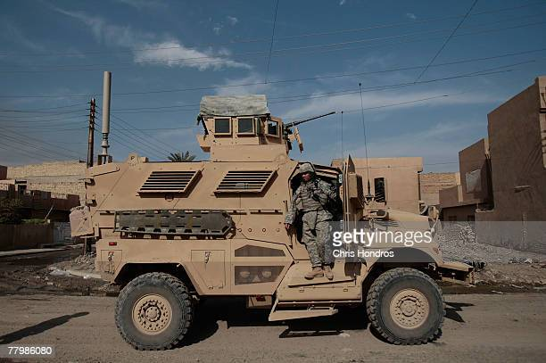 A soldier with the US Army's 212 infantry stands on a MRAP vehicle while on patrol November 17 2007 in Baghdad Iraq MRAPs are a family of...