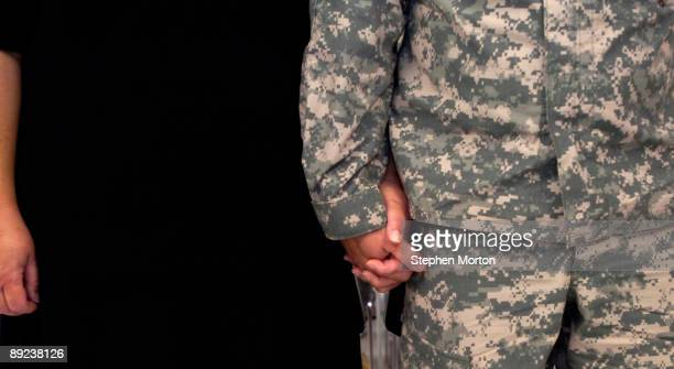 Soldier with the U.S. Army's 293rd Military Police Company holds hands with his wife during the 3rd Infantry Division's first Coin Covenant Ceremony...