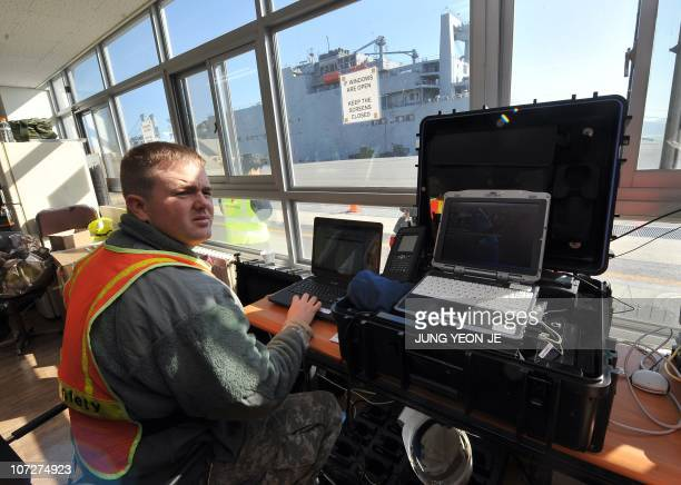 A US soldier works at an operation control centre in front of the US Naval Sealift ship Watson during a download training exercise by the US 403rd...