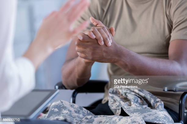 soldier wrings hands while talking with counselor - military doctor stock photos and pictures