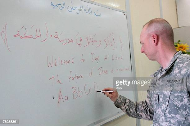 S soldier write on a board during the opening of Dar AlHikmah a juvenile detainee education facility at the US military Camp Victory August 14 2007...