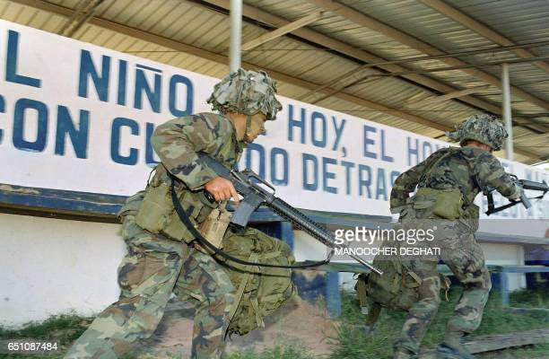 Soldiers advance toward their position at a military command post loyal to General Manuel Antonio Noriega 23 December 1989 in Santiago, 200 miles...