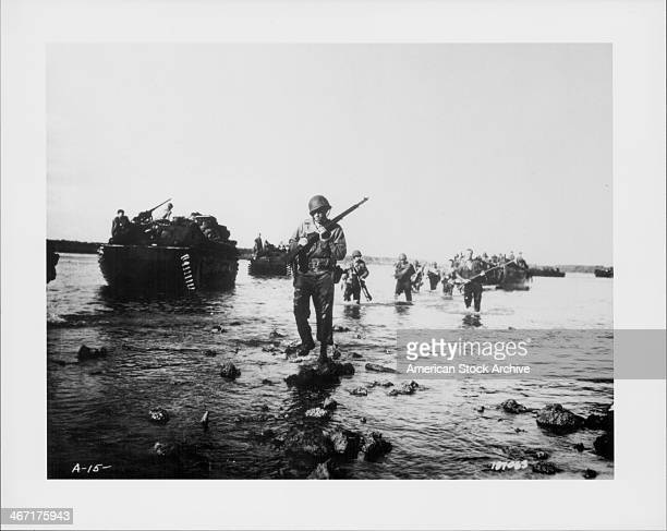 US soldiers advance towards land from the beaches at Normandy DDay World War Two France June 6th 1944