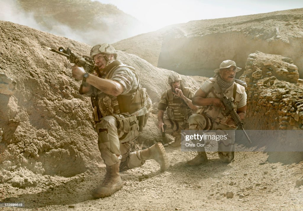 Soldiers advancing in dry rural landscape : Stock Photo