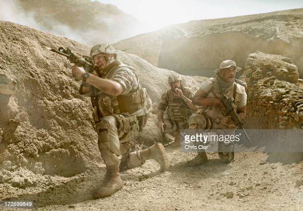 soldiers advancing in dry rural landscape - war stock pictures, royalty-free photos & images