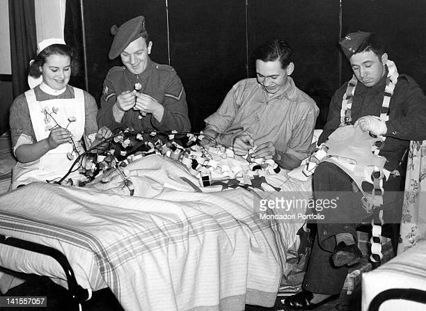 Soldiers and a male nurse decorating a military hospital for Christmas. Surrey, Great Britain, December 1939
