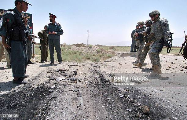 US soldiers and Afghan policemen inspect the site of a suicide attack near the main US base in Afghanistan at Bagram some 50 kms north of Kabul 26...