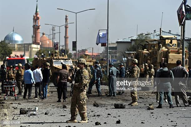 NATO soldiers and Afghan security forces inspect the scene of a suicide car bomb attack that targeted foreign military vehicles at JoeSher in Kabul...