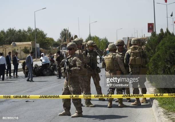 US soldiers and Afghan security personnel investigate the site of a car bomb attack that targeted a NATO coalition convoy in Kabul on September 24...
