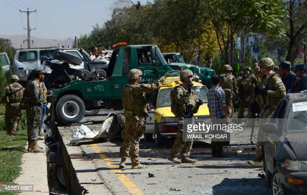US soldiers and Afghan security personnel stand at the site of a suicide attack in Kabul on September 16 2014 A Taliban suicide bomber rammed an...