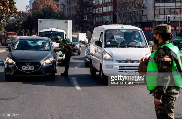 Soldiers and Chilean police members control drivers at a check-point during the mandatory total quarantine due to the new COVID-19 coronavirus...