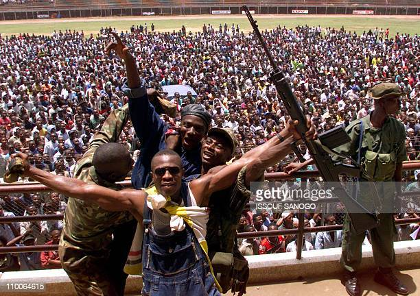 Soldiers and civilians pose in front of the crowd in Freetown's stadium 07 May 2000, during a rally called by former military leader Johnny Paul...