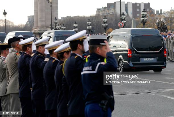 Soldiers and Gendarmes salute as the funeral convoy passes on Alexandre III Bridge in front of the Invalides monument in Paris on December 2 ahead of...