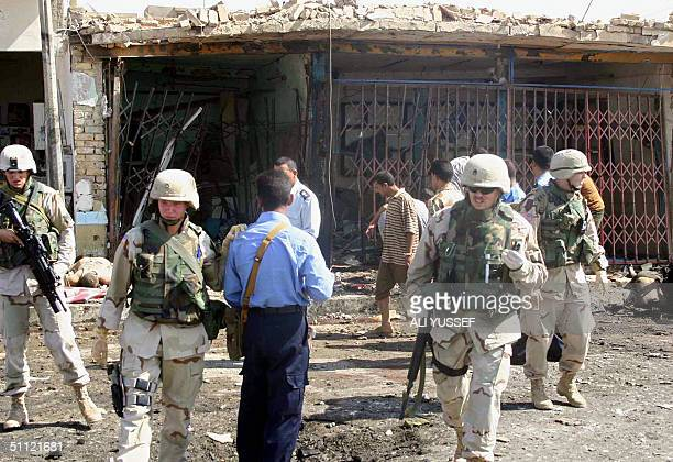 US soldiers and Iraqi policemen inspect the site of a suicide car bombing outside a police station in Baquba 60 kms northeast Baghdad 28 July 2004 At...
