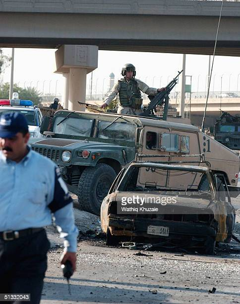 S soldiers and Iraqi policemen secure the scene of a car bomb explosion September 21 2004 in Baghdad Iraq A car bomb exploded near a US military...
