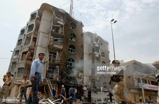US soldiers and Iraqi policemen secure the scene of a car bomb explosion outside an electrical goods store in a busy street in the Karradah district...