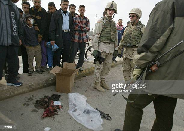 US soldiers and Iraqis stand by human remains after a suicide car bomber blew himself up outside a police station in Baquba 50km northeast of Baghdad...
