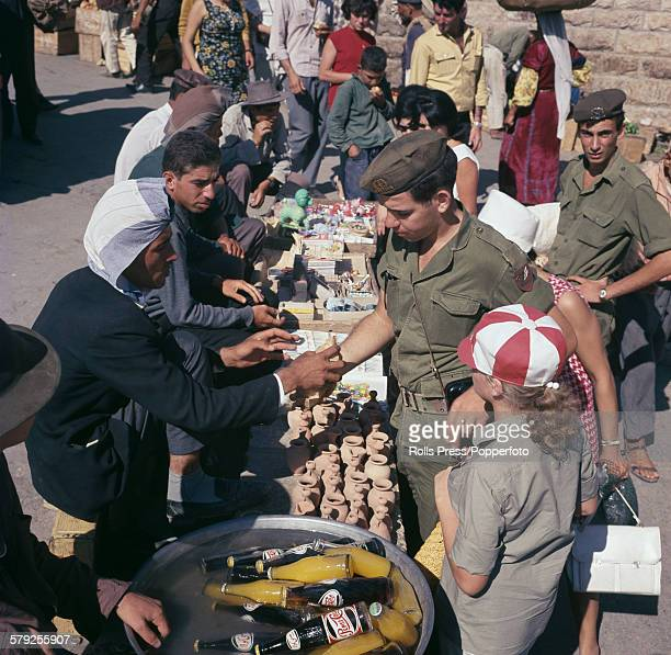 Soldiers and members of the Israel Defense Forces pictured buying items from arab street traders in the city of Jerusalem after the end of the Six...