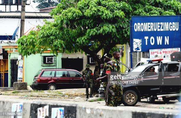 Soldiers and paramilitary men stand guard on the road leading to the Independent National Electoral Commission headquarters in Port Harcourt Rivers...