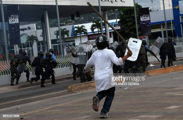Soldiers and police officers in riot gear run away from supporters of Honduran presidential candidate for the Opposition Alliance against the...