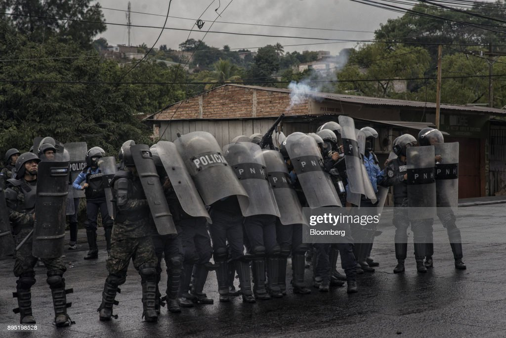 Soldiers and police officers shield themselves from the rocks thrown during protests against the presidential election of Juan Orlando Hernandez in Tegucigalpa, Honduras, on Monday, Dec. 18, 2017. Honduran electoral authorities declared incumbent Hernandez the winner of the Nov. 26 presidential vote after three weeks in which the nation slid into chaos as ballots were counted and recounted. Photographer: Juan Carlos/Bloomberg via Getty Images