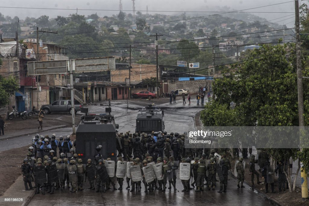 Soldiers and police officers stand with their shields as protesters throw rocks during protests against the presidential election of Juan Orlando Hernandez in Tegucigalpa, Honduras, on Monday, Dec. 18, 2017. Honduran electoral authorities declared incumbent Hernandez the winner of the Nov. 26 presidential vote after three weeks in which the nation slid into chaos as ballots were counted and recounted. Photographer: Juan Carlos/Bloomberg via Getty Images